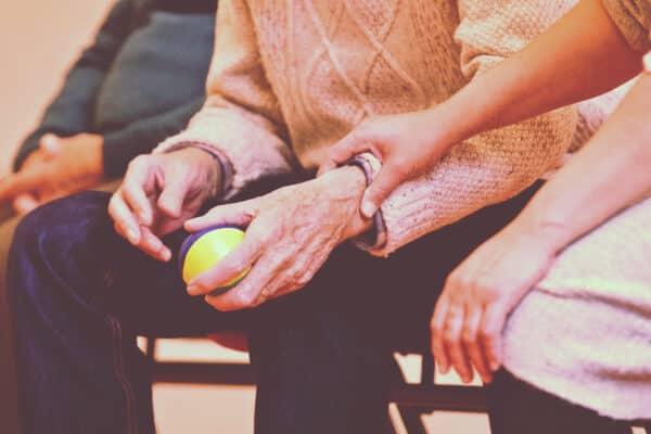 cuidadora con anciano en las palmas