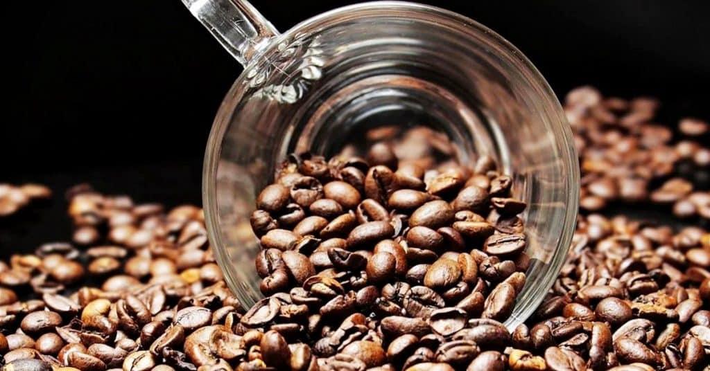 taza de cristal llena de granos de cafe